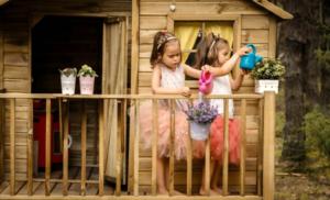 Niñas jugando en caseta de madera