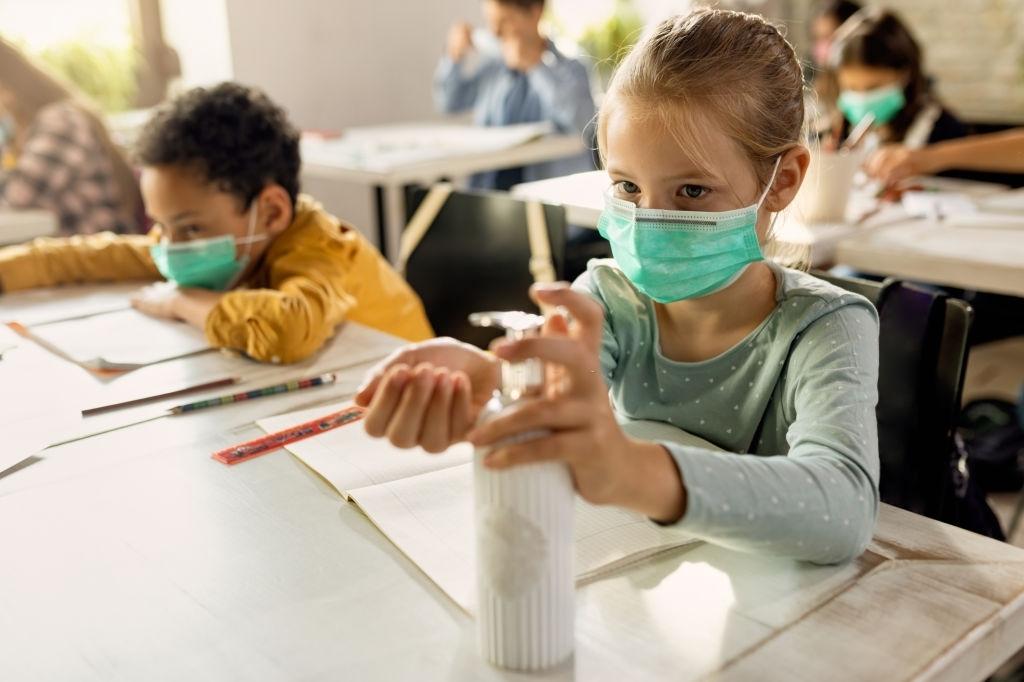Niña desinfectándose las manos en el colegio
